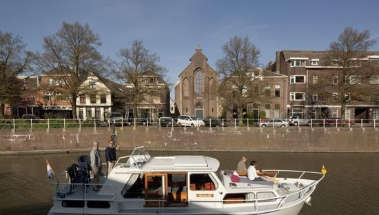 Old Dutch church converted into a beautiful house - View of a boat on a typical Dutch canal  -  by Zecc Architects