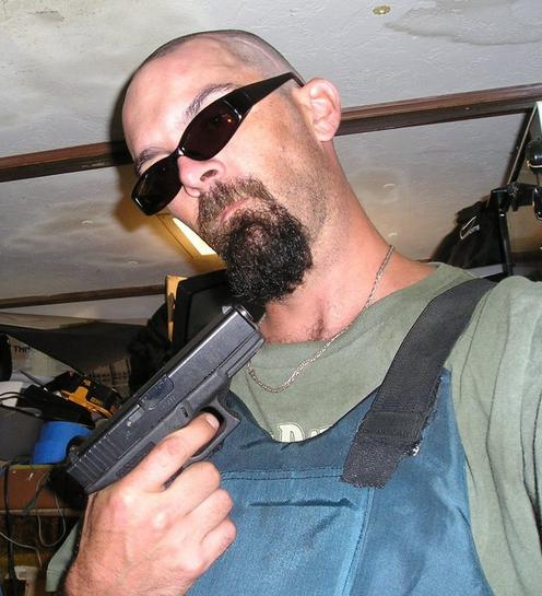 Goateed and shaded Glock owner proudly displays his Glock gun