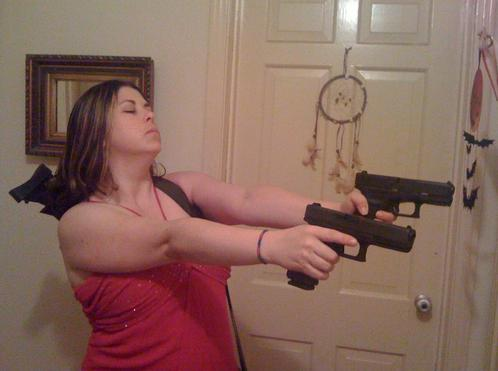 Chick waring a red nightie points not one, but two Glocks with her eyes closed no less