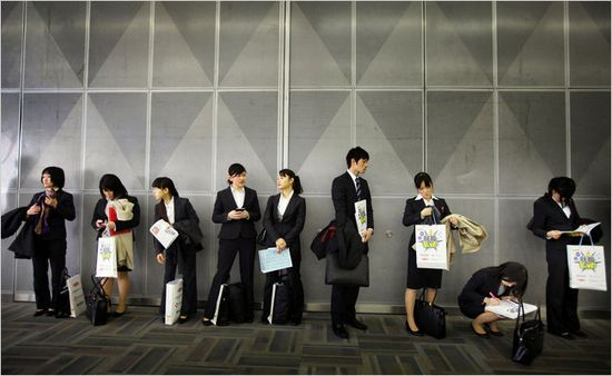 Japanese university graduates wait to attend a company's briefing session during a job fair in Tokyo