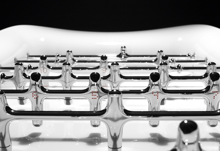 The Beautiful Game foosball table close-up view of its chrome ball paddles against a white luminescent table surface