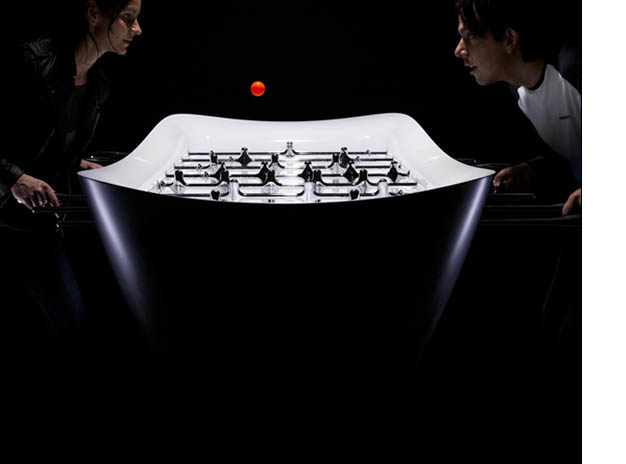 The Beautiful Game foosball table with a gal and guy playing