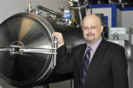 Jeff Edwards stands next to an alkaline hydrolysis device that uses lye and heat to dissolve a body as an alternative to burial or cremation.