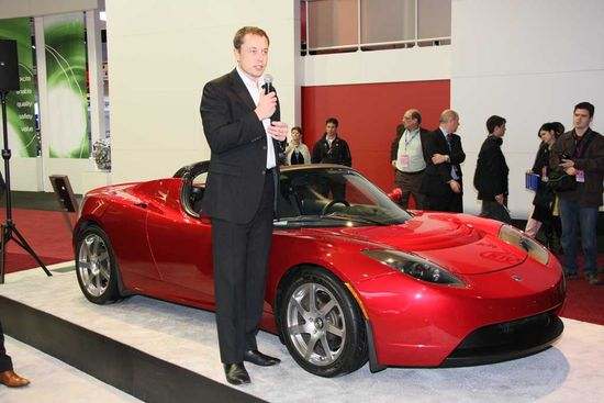 Tesla Motors CEO Elon Musk alongside the Roadster all-electric sportscar
