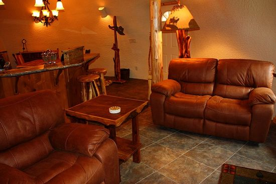 The Hobbit House living room has a granite tiled floor and leather sofa and chair. Cozy