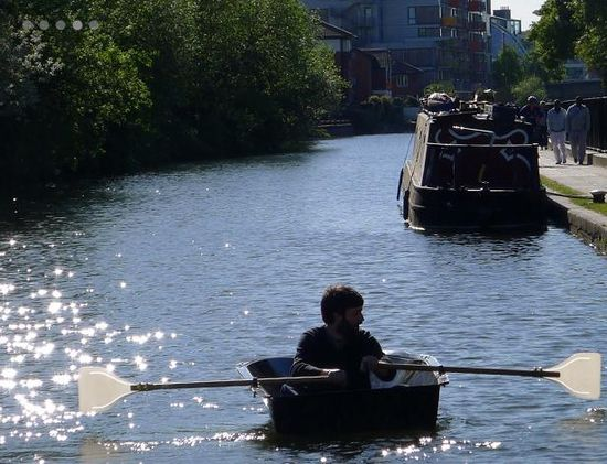 Floatboat being rowed down a London canal