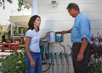 Hydropoint Data Systems contractor assists a homeowner with a WeatherTRAK controller