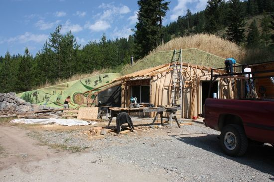 The Hobbit House under construction with earth covering the dome and murals being painted