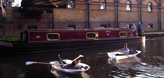 Floatboat being rowed in a canal in London