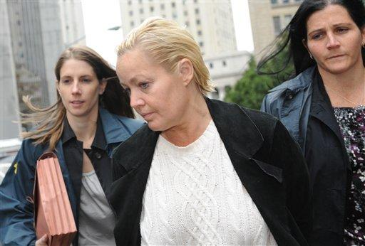 Danielle Chiesi is led in handcuffs from FBI headquarters in New York Friday, Oct.16, 2009