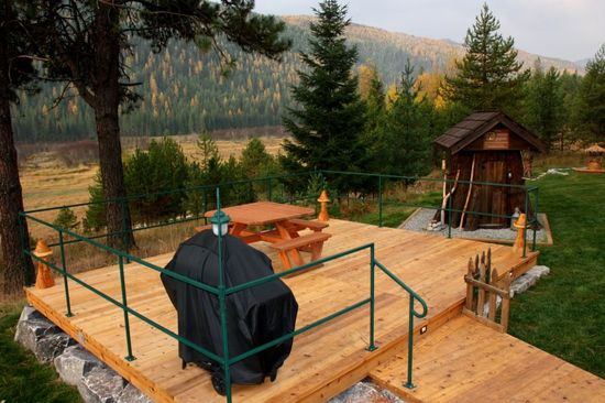 The outdoor wooden deck has a wooden table, green metal barrier and BBQ.and overlooks the house