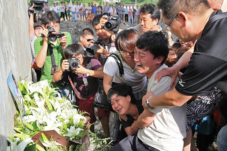 Grieving relatives and loved ones of those killed in the Chinese bullet train crash gather at a memorial to the victims