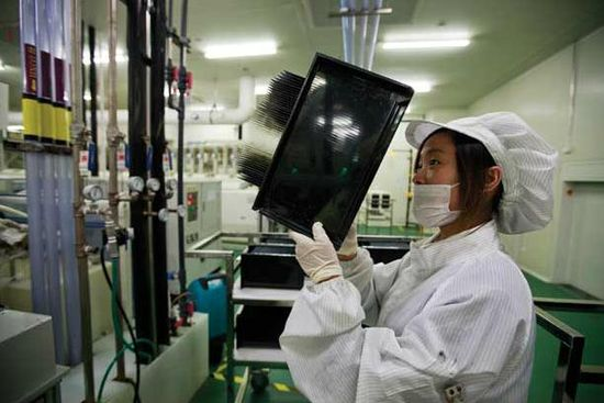 A Chinese solar plant worker inspects the wafers after they've been etched
