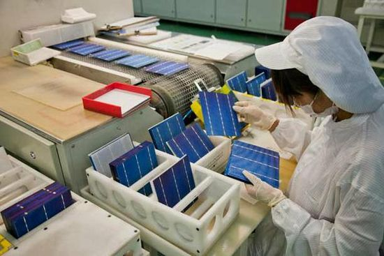A Chinese solar plant worker sorts solar cells by appearance as they emerge from a machine that produces electrical contacts