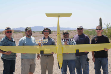 The Autonomous Deployment Demonstration program team holds a Tempest UAV against two, CICADA Mark III gliders.
