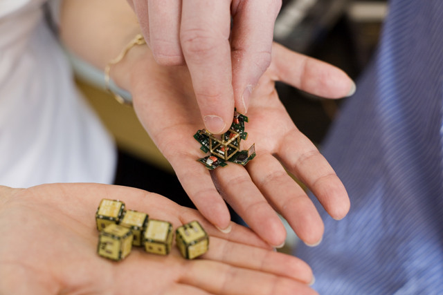 Four duplicate folding cubelet 'smart pebbles' prototypes held in the right hand were made from the original held in the left hand