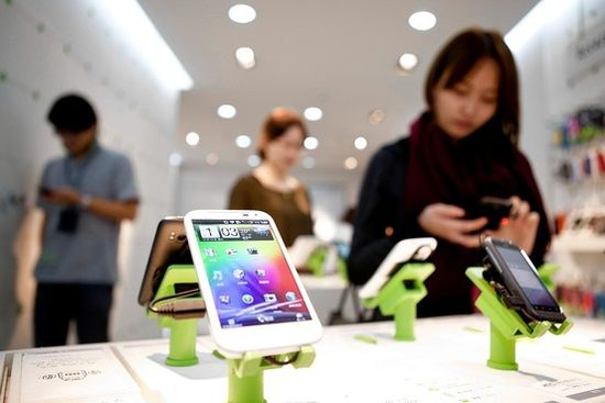 HTC said it would soon remove an infringing feature from its phones. Above, shoppers view HTC phones in a Taipei, Taiwan, store last week.