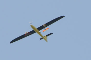 Tempest UAV releasing a CICADA Mark III glider from its left wing. A CICADA Mark II prototype is carried beneath the Tempest's right wing
