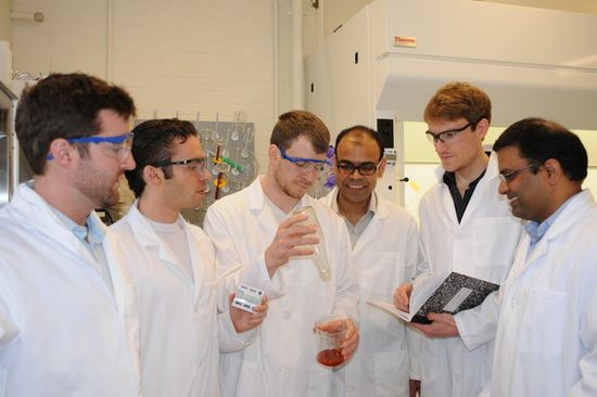 MIT PhD candidate Dave Smith and his research team gather around to demostrate the non-stick properties of LiquiGlide