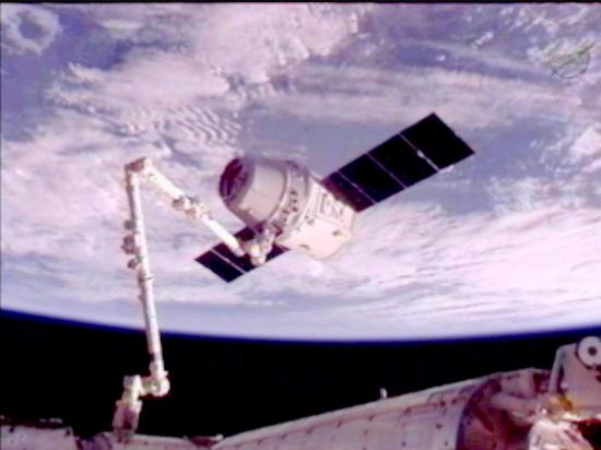 The ISS grapple arm holds the SpaceX's Dragon spacecraft prior to docking maneuveur