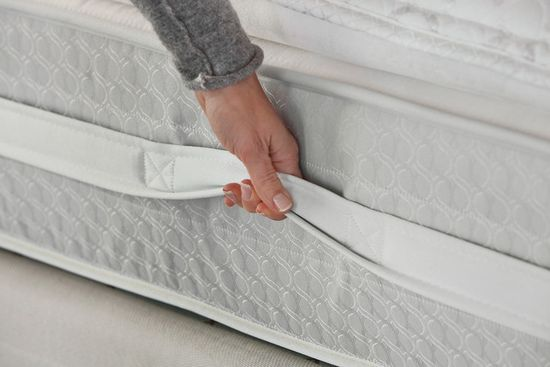 New Sealy Posturepedic mattress has a wraparound handle for easy lifting, and a rubber surface on the bottom to grip the sheets to prevent sheet creep