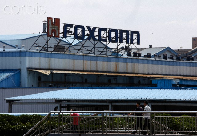 Workers walk outside Hon Hai Group's Foxconn plant in Shenzhen, China.  Foxconn manufacturers the Apple iPhone, iPad and iPod