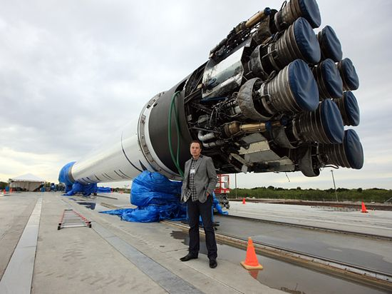 SpaceX CEO and founder Elon Musk stands along side the Falcon 9 rocket