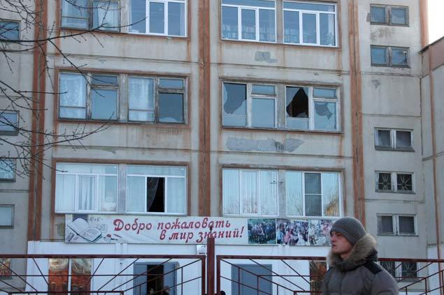 A man walks past a building with shattered windows after a meteorite shock wave in Chelyabinsk, Urals, Russia
