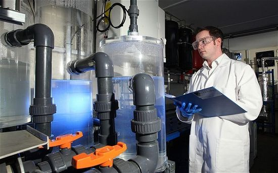 Air Fuel Synthesis technician takes notes as he checks its oil synthesizing machine