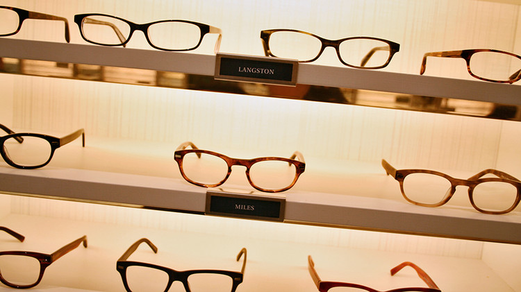 Warby Parker eyewear is prominantly displayed on well-lit shelves for close inspection and test wearing by customers