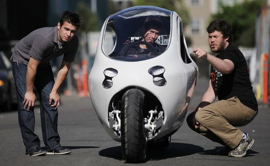 A prototype of Lit Motors'C-1 fully-enclosed and all-electric motorcycle is equipped with a dual gyro stabilization system to keep the bike upright even while stationary