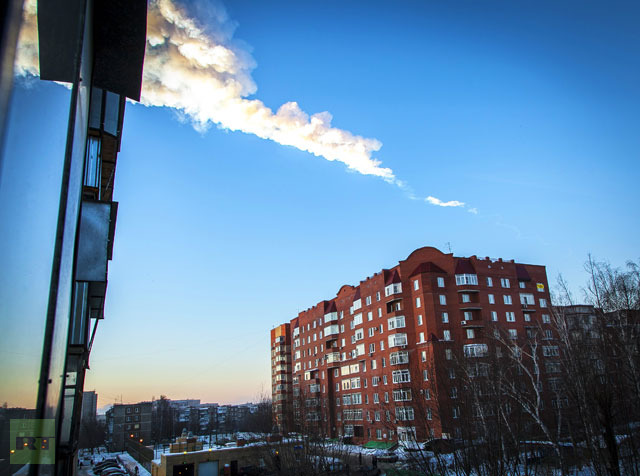 The trail of a falling object is seen above a residential apartment block in the Urals city of Chelyabinsk, on February 15, 2013.(AFP Photo - Oleg Kargopolov)