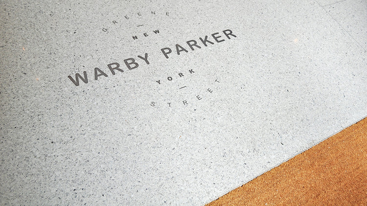 Custom terrazzo flooring embedded with the Warby Parker logo. Partners & Spade dreamed up the store's design conceit