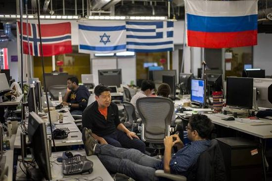 Sitting below flags from around the world, growth team member George Lee, left, speaks with Vishu Gupta at Facebook's HQ. The company is pushing its global reach. (David Butow, LA Times) - October 31, 2012