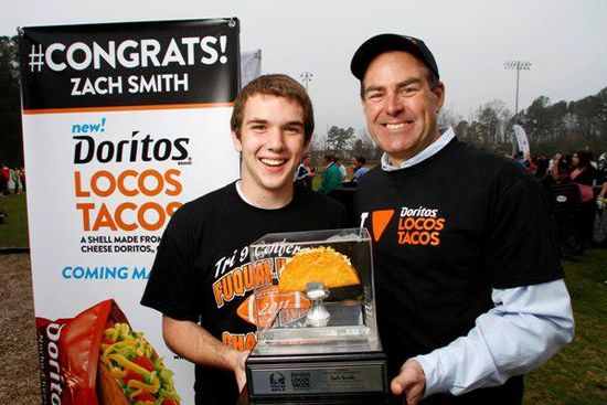 Taco Bell Chief Operating Officer Rob Savage, right, presented a customized trophy to Zach Smith, who won a tweet contest for Doritos Locos Tacos