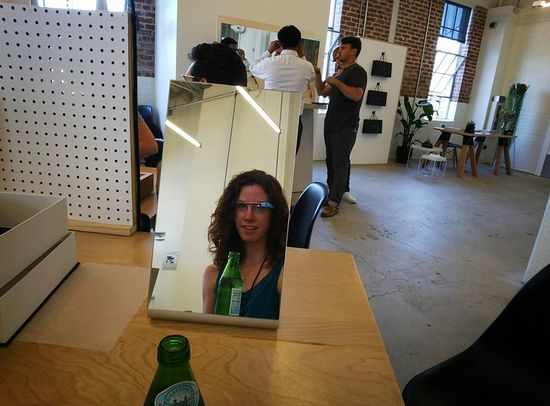Margo tries on a light blue pair of Google Glass glasses and checks how the new augmented reality glasses look on her in a mirror.