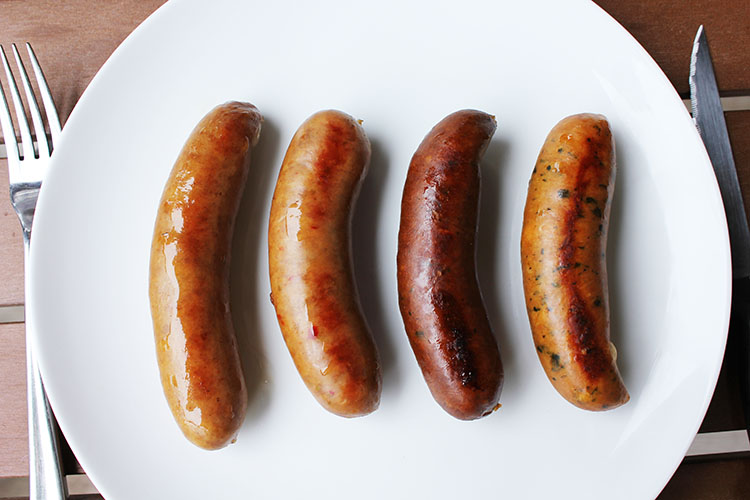 They'll come in four flavors (left to right)--Traditional Bratwurst, Heirloom Italian Brat, Spicy Espresso Brat, and Greek Feta Brat. Each is infused with Dogfish Head beer.