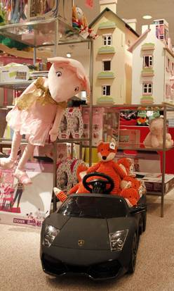 The Neiman Marcus children's department includes unique gifts such as a Lamborghini battery-operated kid's-size black convertible for $395 and wooden doll houses priced at $250 and $350