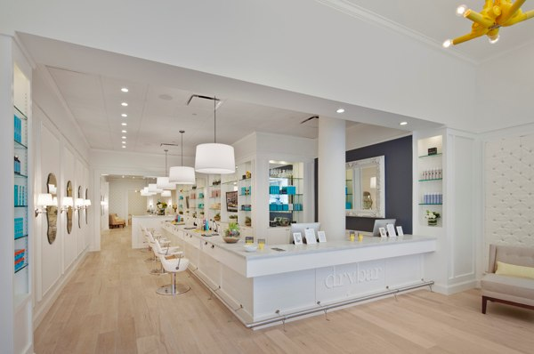 Typical Drybar salon layout includes a lot of white colors throughout, bright lighting and very slick blow drying stations and equipment