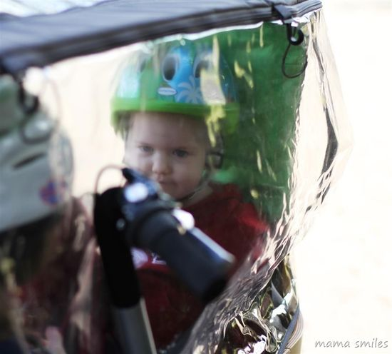 A small child peers out of the front-wheel mounted carrier of the Taga bike