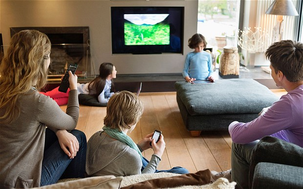 Family watches TV while viewing a second or third digital screen like a tablet or smartphone