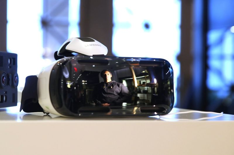 Avinash Changa, WeMakeVR's chief executive, is  reflected on the glass of the firm's Falcon virtual reality device